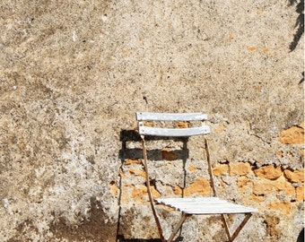 French bistro chair against an old wall (Colméry, France)