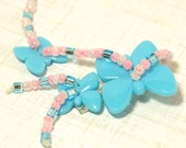 Butterfly beaded barrette that will delight the little girl in your life.  It has 3 light blue and lovely pink  and light blue dangles.