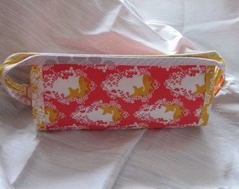A super useful bag with so many zippers. Orange, gold and coral pattern with three individual zippered pockets