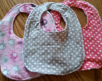 Baby/toddler bibs made from cotton and towel materials with velcro at top.