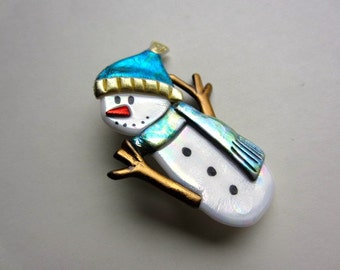 Snowman with twig arms, teal hat, and scarf pin brooch