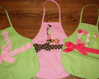 Appliqued Initial Aprons and Girly Smocks with Letters, Ribbon and Bows from Miss Priss & Co. They Make Fun Personalized Gifts