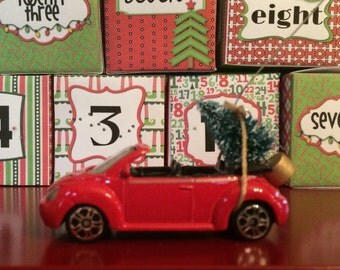 VW bug convertible carrying Christmas tree ornament