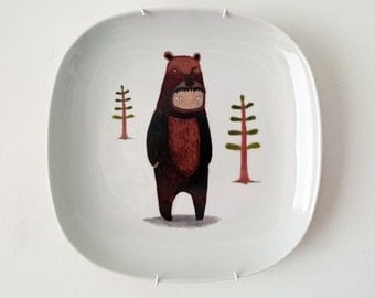 Child in a bear suit illustration on a ceramic plate