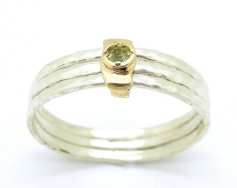 Peridot ring set in gold stacking hammered silver bands