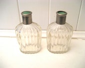 pair of clear glass eau de cologne or aftershave bottles with metal stoppers and lids