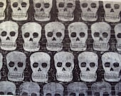 Sheet of black tissue paper linoprinted by hand with skulls