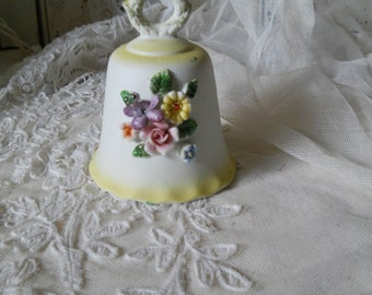 Porcelain Bell With Raised 3D Pink Roses and Flowers Laurel Wreath Handle White Background With Palest Yellow Edges Porcelain Clapper Inside
