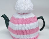 Pink and white striped tea cosy with a pompom for a medium pot.