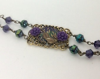 Vintage gold tone shoe buckle bracelet embellished with green and purple painted embossed metal.