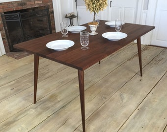 Black walnut dining table, mid century modern featuring tapered wood legs.