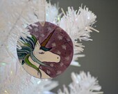 Hand painted ornament featuring a white unicorn with green mane on a metallic background