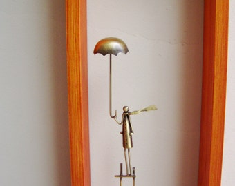 Long wooden frame clock, figure with umbrella on a tall ladder, brass sculpture with a clock in orange, wooden frame, made to order