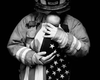 Firefighter holding baby wrapped in American flag in Black and White Photograph