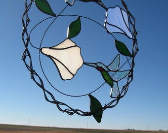 Stained glass oval hummingbird and bell flower suncatcher framed in woven barbed wire