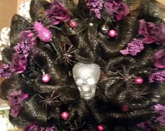 Black deco mesh with purple and black flowers with lighted scull head.