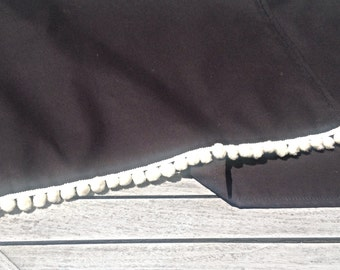 Long black cotton table runner with white pom-pom trim.