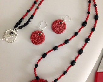 Red and black necklace and earrings set with flower charms.