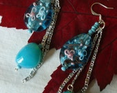 Turqoise blue Lampwork teardrop dangle earrings accented with silvertone chain and coordinating turquoise glass nugget