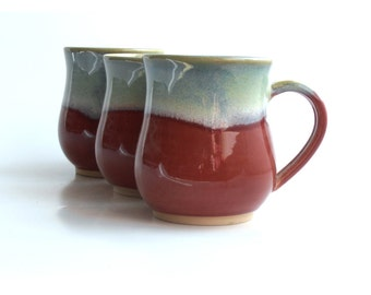 Three small red mugs with aqua accent