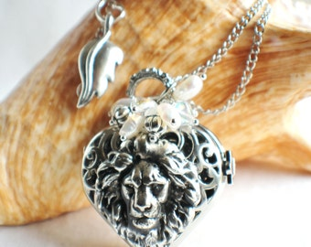 Heart watch locket in silver tone with lion head mounted on front cover of watch.