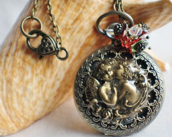 Cupid watch pendant, pocket watch with cupids mounted on front cover.