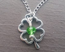Silver 4 leaf clover necklace with a touch of green for St. Patrick's day.