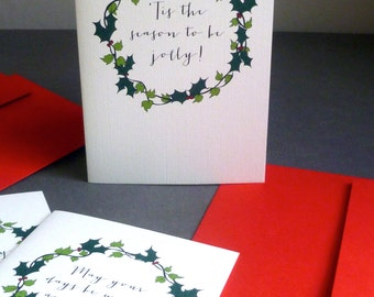 5 Hand-drawn Holly & Ivy Wreath Christmas Card designs, each with a different greeting and red envelope.