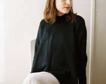 Black turtleneck sweater with dropped shoulder and open sides with seashell buttones / 'Maria'