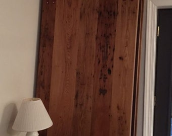 Wormy chestnut rolling interior barn door with Louden double strap rollers from 1901