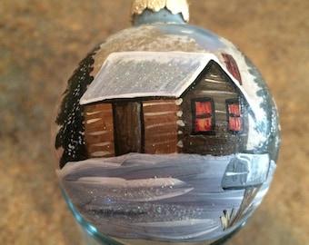 Glass ornament with a cabin scene