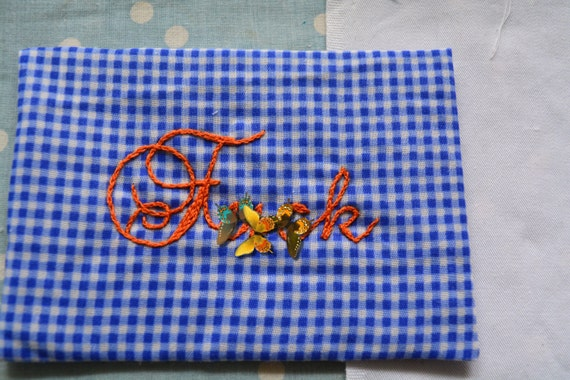 Naughty word hand embroidered on innocent gingham by