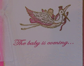 The baby is coming... riding on the stork. Pink and white baby girl card, Let's shower her with Gifts
