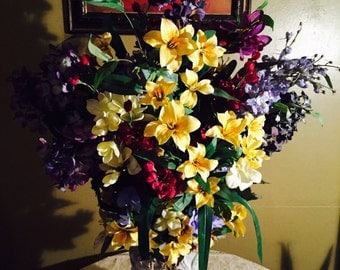 Gold, and yellow Lillies with assortment of deep plum, deep reds with lavender flowers in stone vase with scrolls.