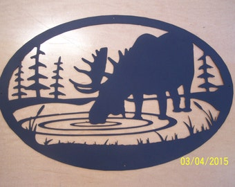 Metal cutout of bull moose drinking from pond.