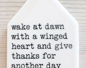 porcelain tag screenprinted text wake at dawn with a winged heart and give thanks for another day. -kahlil gibran