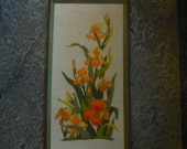 vintage framed stitchery, iris in orange, gold and yellow, 17 1/2 by 32 1/2.