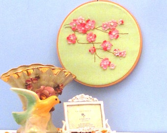 Hoop art of pink blossom branch with beaded embroidered flower centers on pale lime green fabric