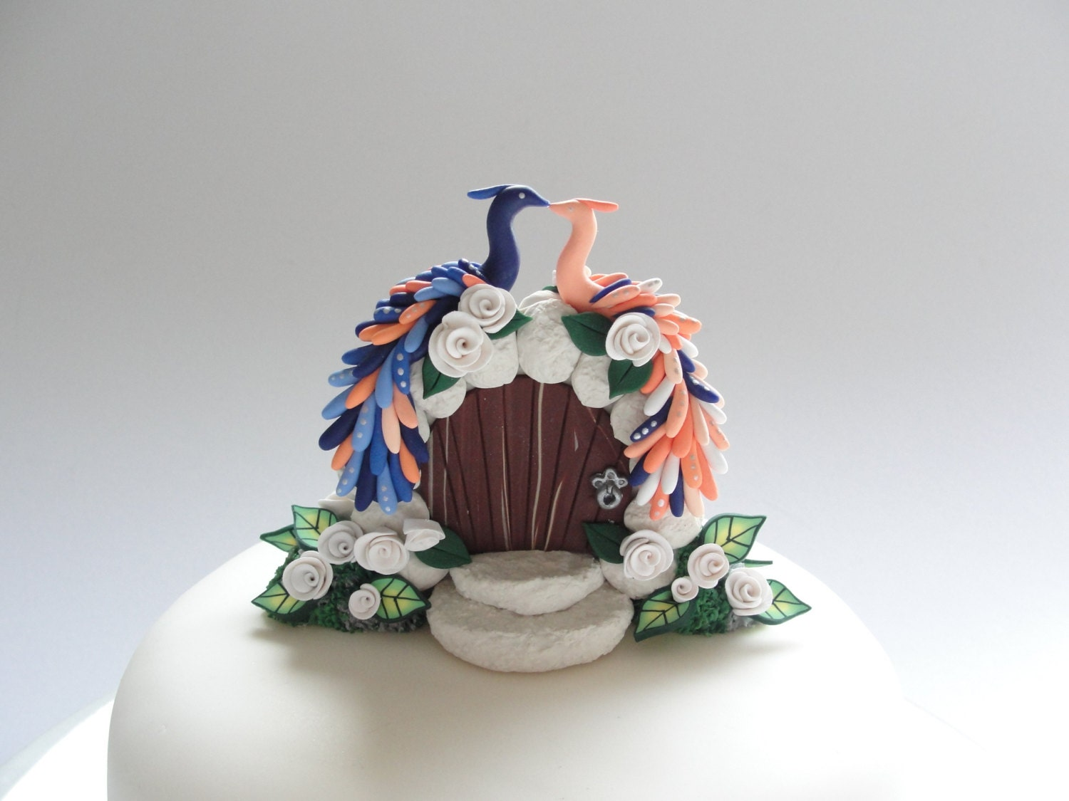 Navy blue and peach peacock themed wedding cake topper