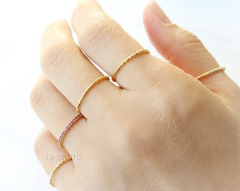 Set of 5 rings- 4 gold twisted rings and a ruby color CZ ring