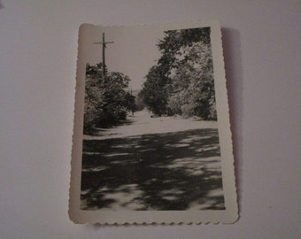 Vtg B&W photo of antique car driving away on road with power line or telephone pole on side.