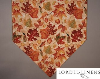 Fall Table Runner with fall leaves scattered on a light cream and tan background with Metallic Accents