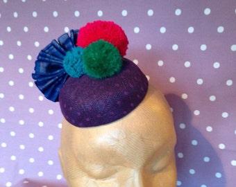 Handmade circus pom pom headpiece/fascinator, polkadot sinamay base, ikat fabric fan. Perfect for weddings and parties!