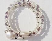 Memory wire bracelet cream glass seed beads, freshwater pearls and purple crystals. Extendable