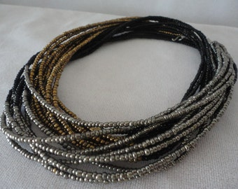 A Multi Strand of Beads In Gold, Silver And Black Color.
