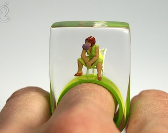 Bubble Gum Queen – Cheeky figures ring with a mini-woman sitting on a chair, making a chewing gum bubble, on a green ring made of resin