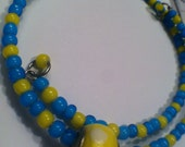 Beautiful wrap bracelet with small blue and yellow beads, with a yellow polk-a-dot European charm bead