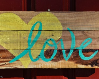 "Reclaimed wood sign with yellow heart and teal ""love""."