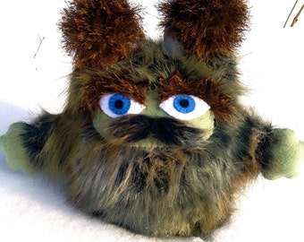 Camolot the Brumblewump. Caretaker of the Troublewumps - He is Not a Monster!  Camouflage, stuffed animal with a mustache. Book character.