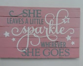 Hand painted wood sign with quote - She leaves a little sparkle wherever she goes. Beautiful pink sign with gray and white lettering.
